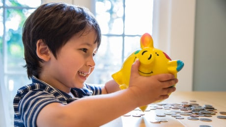 Little boy holds a piggy bank and looks happy with coins on a table